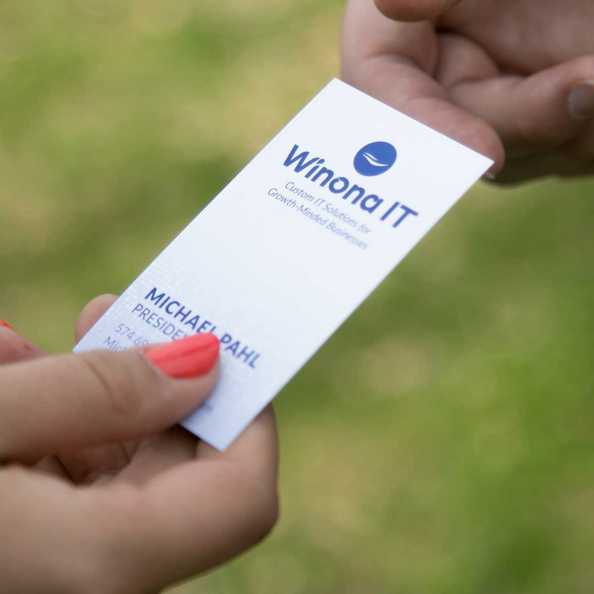 Handing off a business card to provide a point of contact for help with IT strategies.